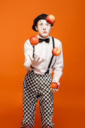Portrait d'un acteur en pantomime avec un maquillage facial blanc montrant des émotions expressives sur fond orange en studio Banque d'images