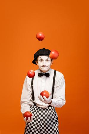Retrato de un actor como una pantomima con maquillaje facial blanco que muestra emociones expresivas sobre el fondo naranja en el estudio