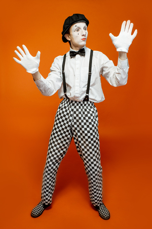 Full length portrait of an actor as a pantomime with white facial makeup showing expressive emotions on the orange background