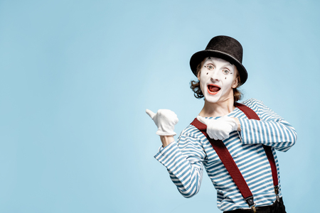 Emotional pantomime with white facial makeup showing empty space on the blue background, advertising something
