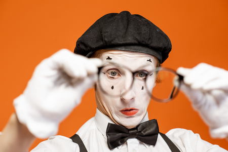 Portrait of a pantomime with white facial makeup in eyeglasses showing expressive emotions on the orange background Archivio Fotografico