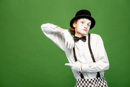 Portrait of an actor as a pantomime with white facial makeup posing with expressive emotions isolated on the green background Stock Photo