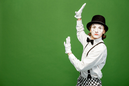 Portrait of an actor as a pantomime with white facial makeup posing with expressive emotions isolated on the green background Banque d'images - 118137268