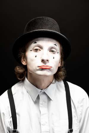 Close-up portrait of a pantomime with white facial makeup posing with expressive emotions on the black background Stock Photo - 118137276