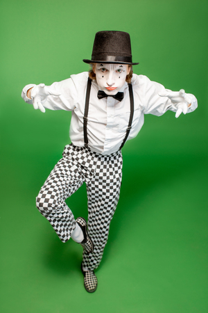 Full body portrait of an actor as a pantomime posing with expressive emotions isolated on the green background