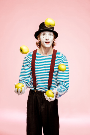 Pantomime with white facial makeup juggling with apples on the pink background in the studio Stockfoto