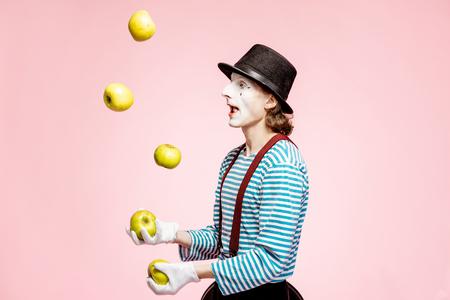 Pantomime avec maquillage facial blanc jonglant avec des pommes sur fond rose en studio