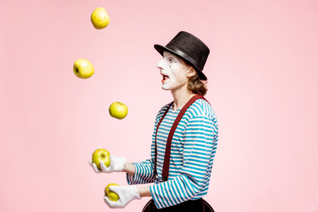 Pantomime with white facial makeup juggling with apples on the pink background in the studio Reklamní fotografie