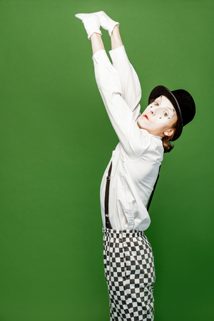 Portrait of an actor as a pantomime with white facial makeup posing with expressive emotions isolated on the green background Reklamní fotografie
