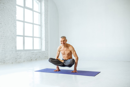 Senior man with naked torso practising yoga in the white studio