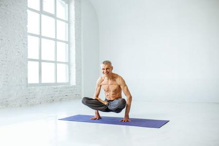 Senior man with torso practising yoga in the white studio
