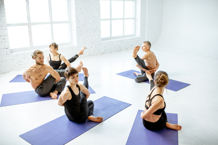 Group of young people practising yoga with experienced senior trainer in the white spacious studio