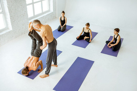 Group of young people practising yoga with experienced senior trainer in the white spacious studio Stock Photo