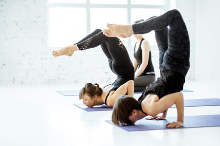 Young and fit people in black sportswear practising yoga in the white fitness studio