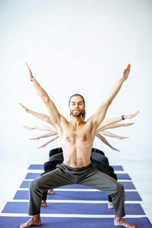 Man with naked torso standing in a yoga pose with multiple arms of other people behind on the white background Stock Photo