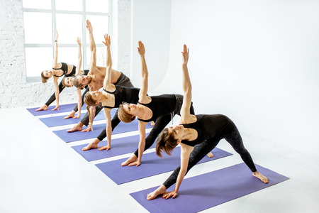 Group of a young people practising yoga standing together in a line in the white studio Stock Photo