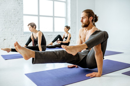 Group of young athletic people practising yoga during the lesson in the white fitness studio