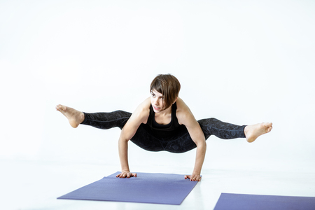 Young woman in black sportswear standing in yoga pose in the white studio