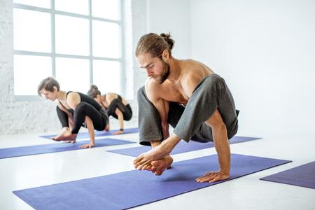 Grupo de jóvenes atléticos practicando yoga durante la lección en el gimnasio blanco Foto de archivo