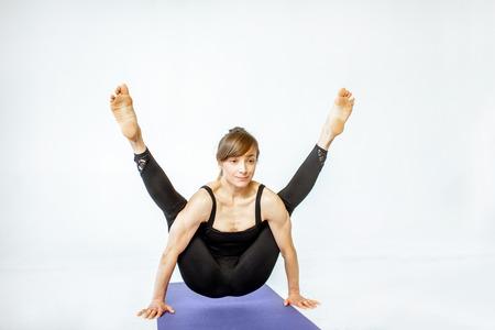 Jeune femme en tenue de sport noire debout dans une pose de yoga dans le studio blanc