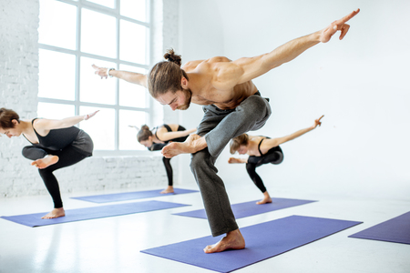Group of young athletic people practising yoga during the lesson in the white fitness studio Stock Photo
