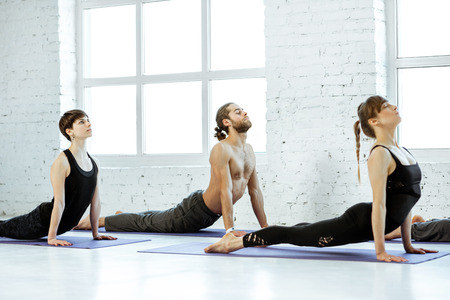 Young group of people practising yoga, stretching in the white spacious studio Stock Photo