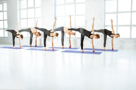 Young group of people practising yoga, keeping pose arranged together in a row in the white spacious studio. Wide view with copy space