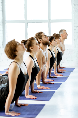 Young group of people practising yoga, keeping pose arranged together in a row in the white spacious studio