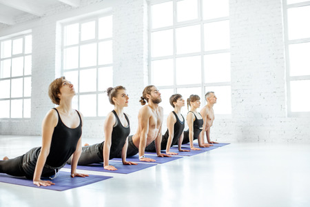 Young group of people practising yoga, keeping pose arranged together in a row in the white spacious studio Stock Photo
