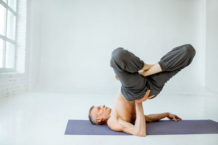 Senior athletic man with nude torso practising yoga poses in the white studio
