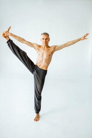 Senior athletic man with exposed  torso practising yoga poses in the white studio Stock Photo