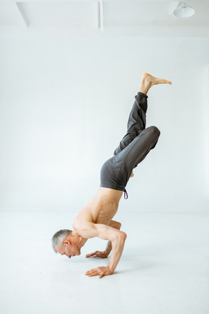 Senior athletic man with exposed torso practising yoga poses in the white studio