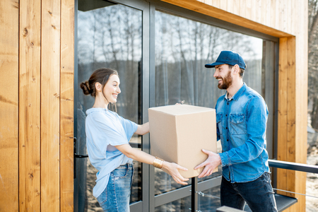 Delivery man bringing packaged goods to a young woman client standing together outdoors in front of the modern house. 写真素材