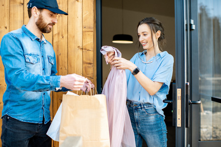 Delivery man bringing some goods packaged in paper bags for a young woman client to home. Buying clothes online and delivery concept Stockfoto