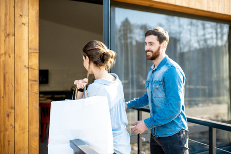 Young couple entering home carrying shopping bags. Happy purchase and modern living concept Imagens