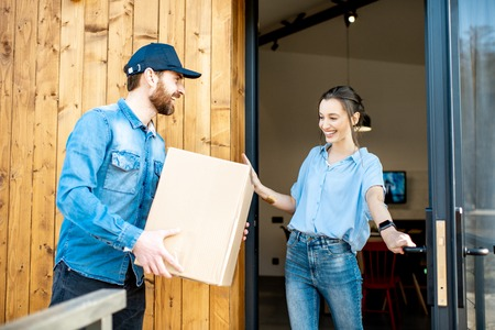 Delivery man bringing packaged goods to a young woman client standing together outdoors in front of the modern house. Stock Photo