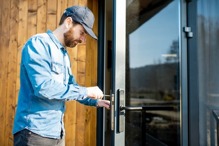 Workman repairing entrance door lock of the modern house or hotel during the sunny weather outdoors Stockfoto