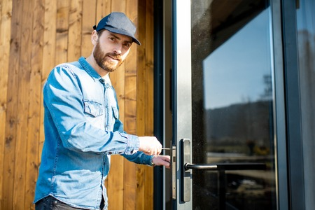 Workman repairing entrance door lock of the modern house or hotel during the sunny weather outdoors Standard-Bild