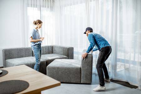 Delivery man mounting new sofa for a young woman client in the modern apartment Stock Photo - 118140048
