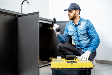 Handyman in blue shirt and cap mounting or repairing kitchen furniture in the apartment