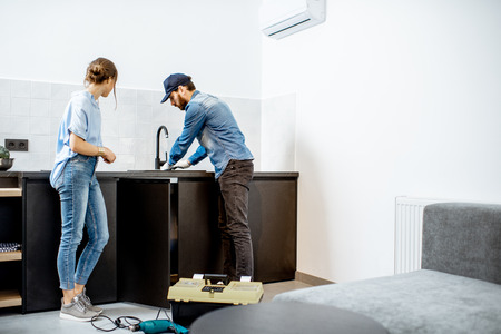 Plumber or handyman repairing kitchen faucet standing with young woman in the apartment. Home repair service concept Stock Photo