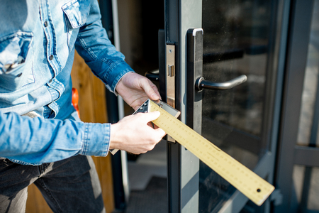Man changing core of a door lock of the entrance glass door, close-up view with no face Stock Photo