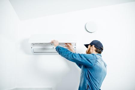 Riparatore in abiti da lavoro blu che serve il condizionatore d'aria che cambia il filtro sullo sfondo del muro bianco