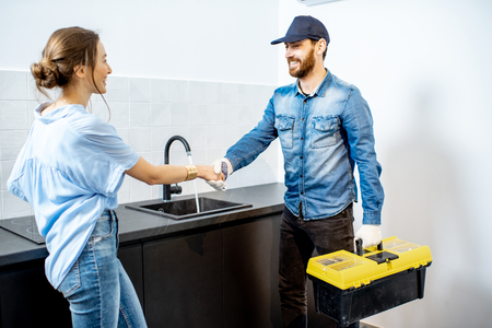 Handy man having a deal with young woman client after the repairment on the kitchen. Home repair service concept Banque d'images - 118140086