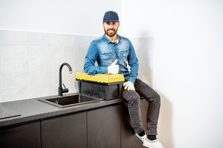 Portrait of a handsome repairman in blue shirt and cap with tool case on the kitchen