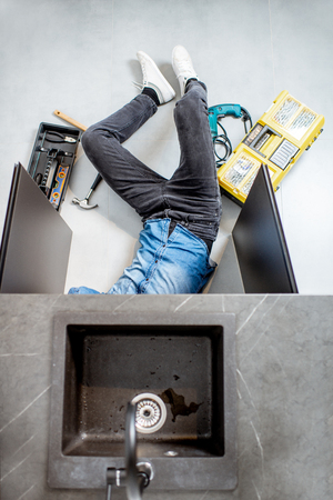 Handyman repairing kitchen plumbing lying under the sink on the floor, view from above Banque d'images - 118140089