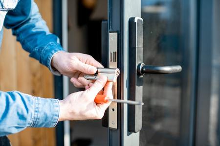 Man verandert de kern van een deurslot van de glazen ingangsdeur, vergrote weergave zonder gezicht Stockfoto