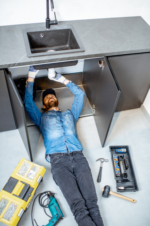 Handyman repairing kitchen plumbing lying under the sink on the floor, view from above Banque d'images - 118140104