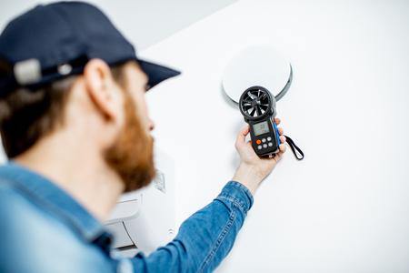 Tuttofare che controlla la velocità della ventilazione dell'aria con lo strumento di misurazione sullo sfondo della parete bianca Archivio Fotografico