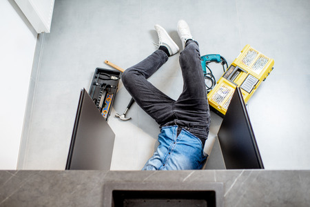 Handyman repairing kitchen plumbing lying under the sink on the floor, view from above Banque d'images - 118140137